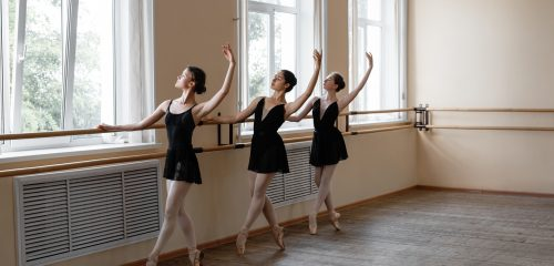 Full body young balled dancers with raised arms tiptoeing and looking away while exercising at barre and window in spacious studio
